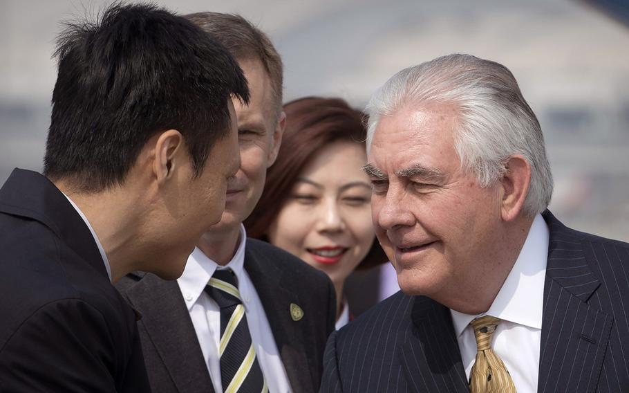 U.S. Secretary of State Rex Tillerson, right, is greeted by officials as he arrives at Beijing Capital International Airport in Beijing, China, Saturday, March 18, 2017.