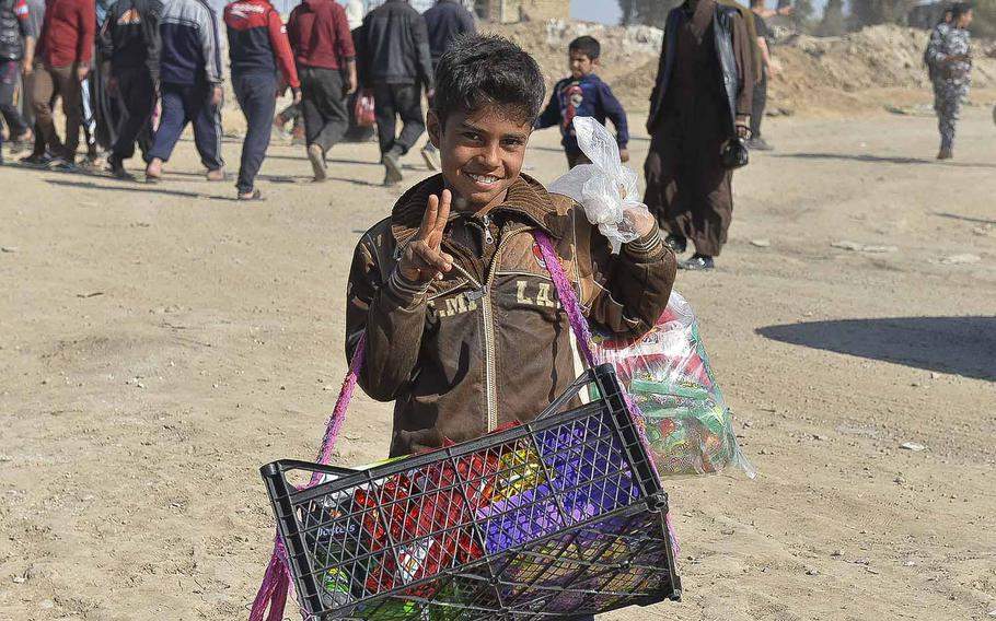 An Iraqi boy flashes a peace sign while selling chips outside a displacement camp in Hama Alil on Thursday, March 9, 2017. Thousands of Iraqis are fleeing Mosul daily as government forces battle Islamic State fighters for control of the city's western districts. The Iraqis declared the half of the city east of the Tigris River liberated in late January.