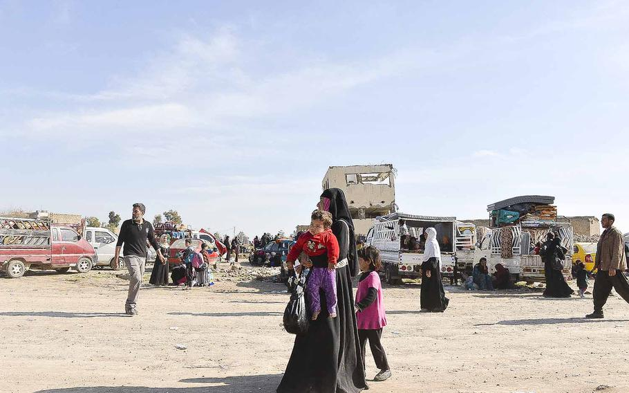 An Iraqi woman carries a child outside a camp for the displaced residents of Mosul on Thursday, March 9, 2017.