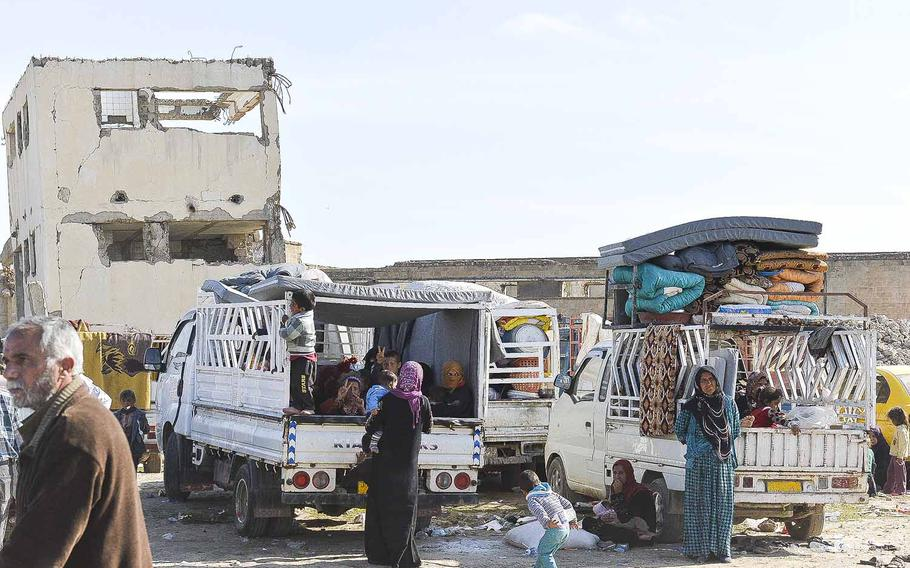 Families fleeing the battle for Mosul wait in trucks outside a camp for displaced Iraqis south of the city on Thursday, March 9, 2017. Thousands of civilians were staying in the camp, but many families were being screened for ties to the Islamic State group before being allowed to flee further from the city.