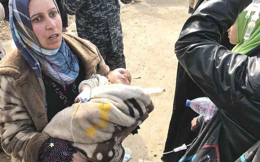 On the outskirts of Mosul, a woman holds her ill infant, who was receiving intravenous fluids, while waiting for transportation to a displacement camp south of the city on Wednesday, March 8, 2017.