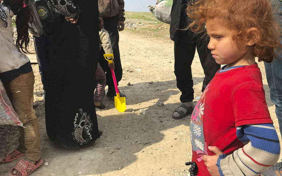 An Iraqi girl waits with her family on Wednesday, March 8, 2017, after they had fled their Mosul neighborhood seeking safety away from where Iraqi military and police are battling the Islamic State for control of the city.