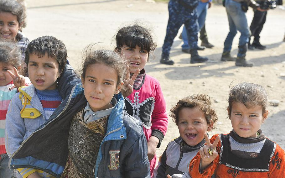 Iraqi children displaced from their homes in Mosul by fighting pose for a photo near the Mosul airport on Wednesday, March 8, 2017. The children and their families were awaiting transportation to a camp south of the city where people were being screened for Islamic State ties and given food and shelter.