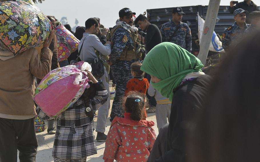 A man and a girl carry bags full of their belongings as they walk toward a truck that will take them to a displacement camp on Wednesday, March 8, 2017. Civilians fleeing violence in Mosul, Iraq were being packed into vehicles and taken to screening points, then on to the camps. Thousands are fleeing each day as fighting intensifies in the western half of the city.