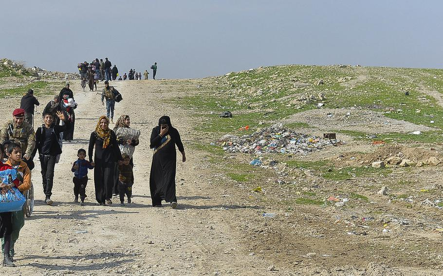 Families fleeing violence in Mosul, Iraq stream over a hill near the city's airport, where Iraqi military and police officials were waiting to pack them onto buses and trucks to be taken to a displacement camp south of the city on Wednesday, March 8, 2017.