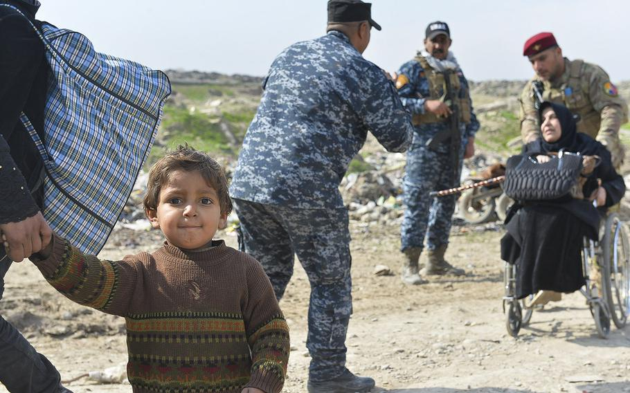 This boy, pictured on Wednesday, March 8, 2017, flees Mosul with his family, as Iraqi security forces assist an elderly woman in a wheel chair. Thousands of Iraqis are escaping the city, taking what they can carry, as Iraqi forces fight to retake it from the Islamic State, which has held it since summer 2014.