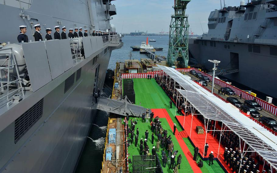 The crew of the JS Kaga attend the helicopter destroyer's commissioning ceremony in Yokohama, Japan, Wednesday, March 22, 2017.