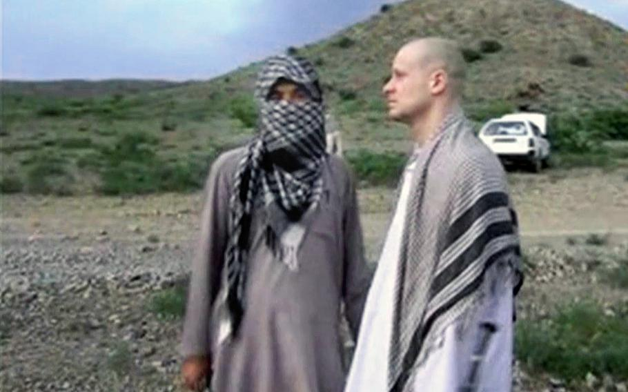 A video screen grab shows Sgt. Bowe Bergdahl, right, standing with a Taliban fighter in eastern Afghanistan.