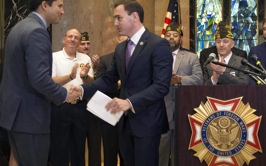 Rep. Mike Gallagher, R-Wis., shakes hands with Rep. Seth Moulton, D-Mass., at the Global War on Terror Memorial press conference, March 28, 2017.