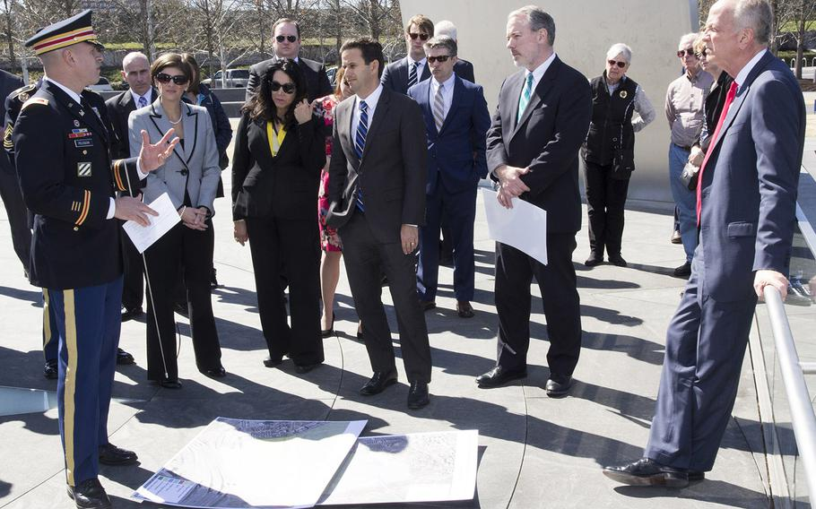 From a vantage point at the Air Force Memorial in Arlington, Va., Col. Michael Peloquin, Director of Engineering at Arlington National Cemetery, explains the cemetery's expansion plans to Senate Appropriations Committee military construction, VA and related agencies subcommittee Chairman Sen. Jerry Moran, R-Kan., right, Ranking Member Sen. Brian Schatz, D-Hawaii, center; subcommittee Majority Clerk Robert Henke, second from right; cemetery Superintendent Katharine Kelley, second from left; and Karen Durham-Aguilera, executive director of Army National Military Cemeteries, third from left.