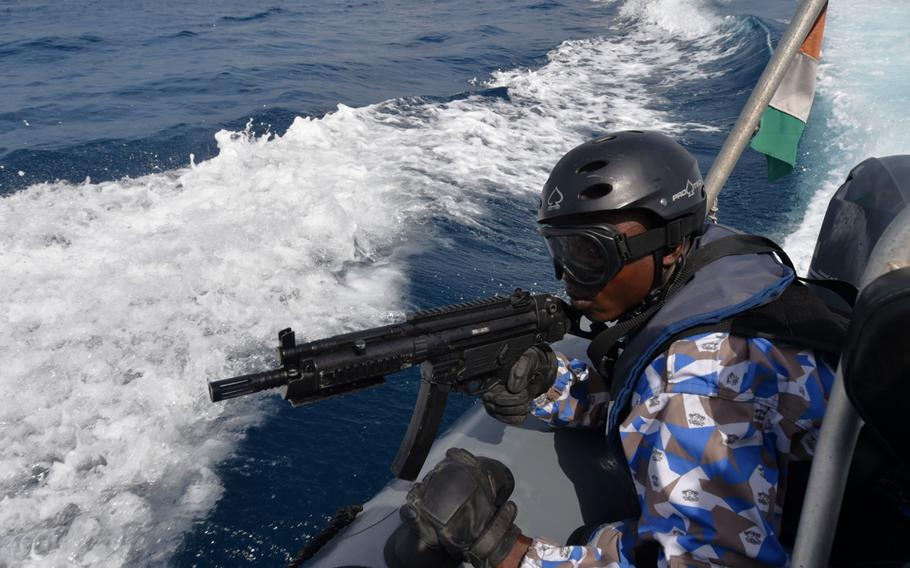 A member of the Ivorian Maritime Interdiction Operations team keeps watch as part of a simulated anti-narcotics search-and-seizure raid during Obangame Express on March 27, 2017.