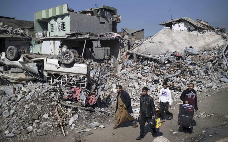 Iraqis walk past debris of houses destroyed during fighting between Iraqi security forces and Islamic State militants on the western side of Mosul, Iraq, Friday, March 24, 2017.
