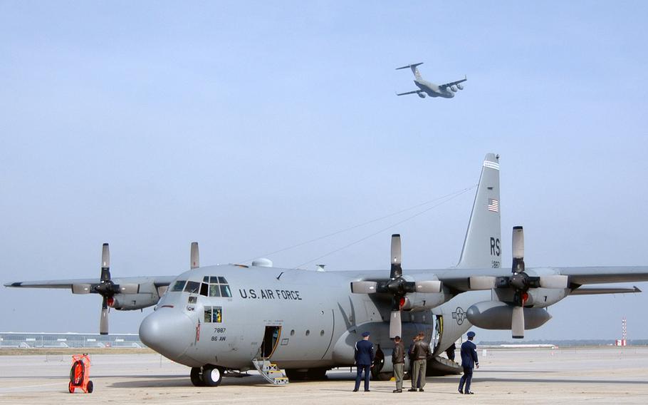 "A U.S. Air Force C-17 Globemaster III, named ""Spirit of Berlin"", passes over Rhein-Main Air Base, Germany, and a Ramstein-based C-130 Hercules, at the Rhein-Main Air Base closure ceremony on Oct. 10, 2005.      (enw# 61p cs)"