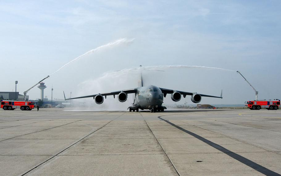"""A U.S. Air Force C-17 Globemaster III, named """"Spirit of Berlin"""", gets a watery salute before taking off from Rhein-Main Air Base, Germany, at the end of the base's closure ceremony on Monday, Oct. 10, 2005."""