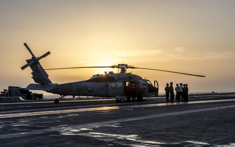 Flight deck crew onboard the aircraft carrier USS George H.W. Bush check a helicopter before take off in the Persian Gulf, April 20, 2017.