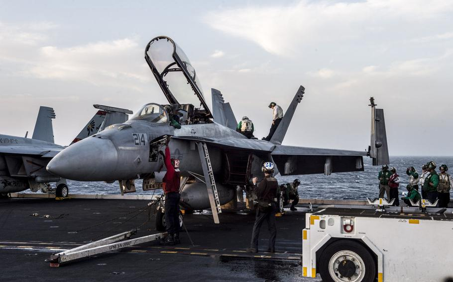 Flight deck crew on board the aircraft carrier USS George H.W. Bush conduct a preflight check on an F/A-18 Hornet in the Persian Gulf, April 20, 2017.
