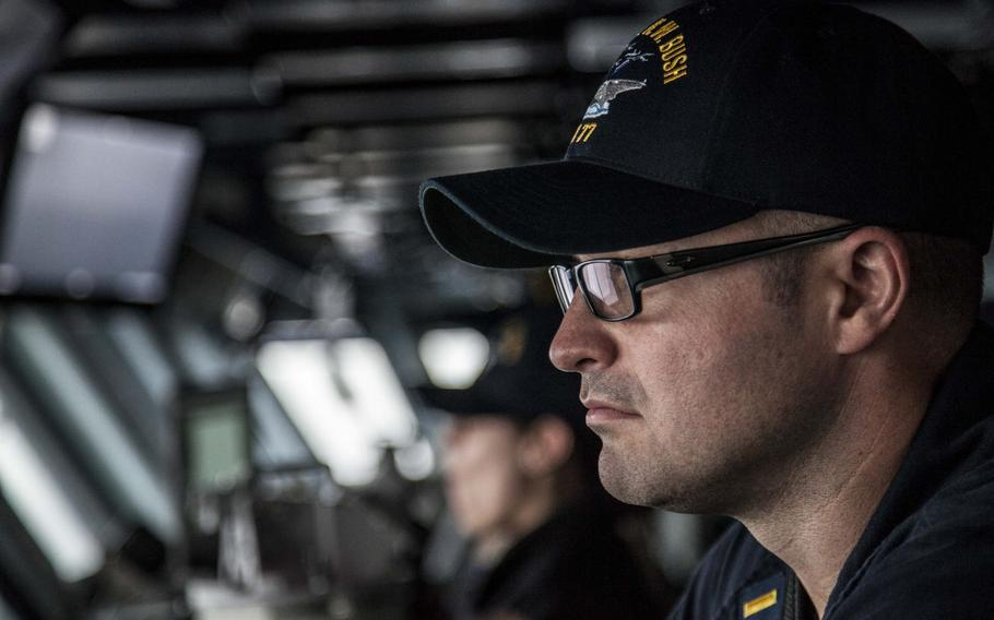 An officer looks out over the flight deck of the aircraft carrier USS George H.W. Bush from the ship's bridge during flight operations in the Persian Gulf April 19, 2017.