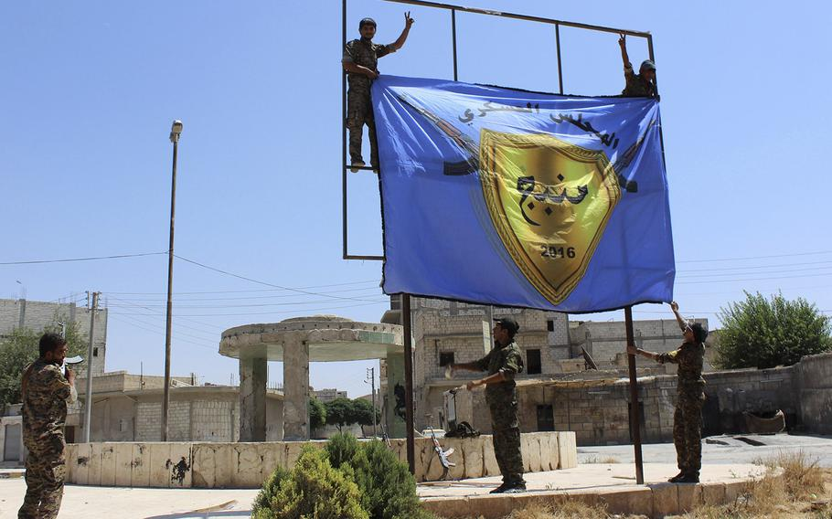 This file photo released on Aug. 8, 2016 by Hawar news, the news agency for the semi-autonomous Kurdish areas in Syria (ANHA), shows Kurdish-led Syria Democratic Forces raising their flag after driving Islamic State militants out of the area, in Manbij, Syria.