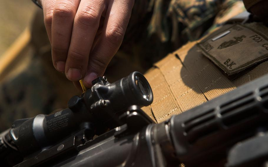 A U.S. Marine with II Marine Headquarters Group adjusts the optics on his M4 during a combat military training shoot on Camp Lejeune, N.C., March 21, 2017.