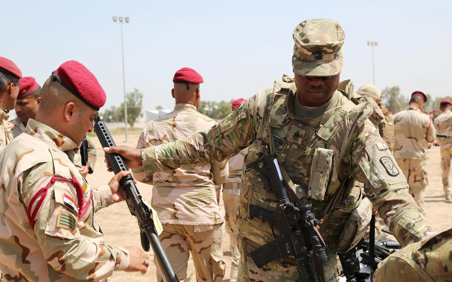 U.S. Army 1st Sgt. Gabriel Montgomery issues an M16 rifle to an Iraqi soldier during an Iraqi Train and Equip Fund issuing point at Camp Taji, Iraq, April 16, 2016.
