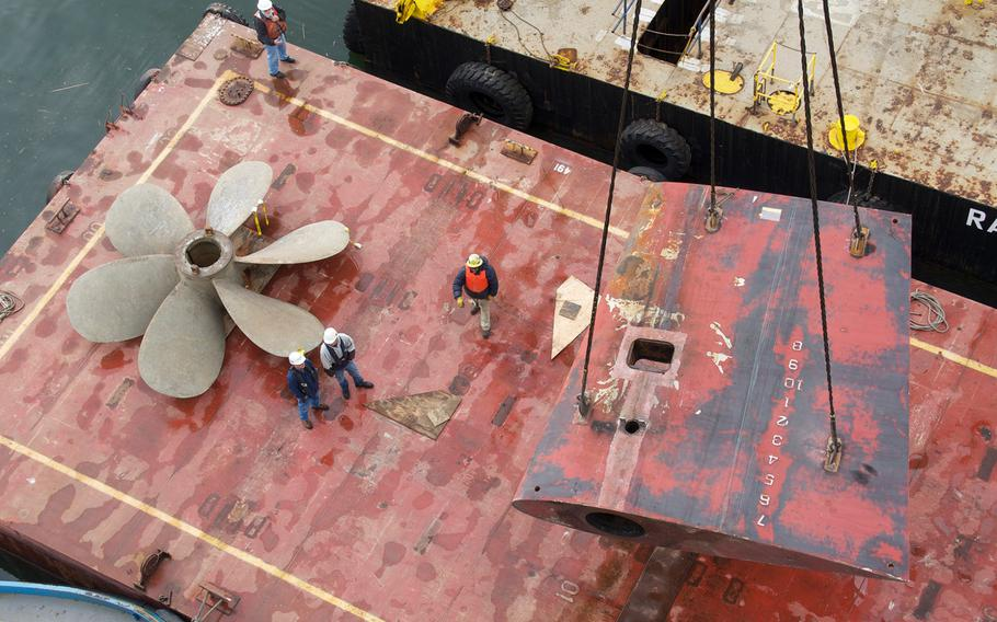 Shipyard workers use a barge crane to move the propellers and rudder of the amphibious assault ship USS Bonhomme Richard in San Diego on Dec. 23, 2010. The Navy wants to hire about 2,000 new shipyard workers to help make more repairs to surface warships, the service announced Thursday, June 1, 2017.