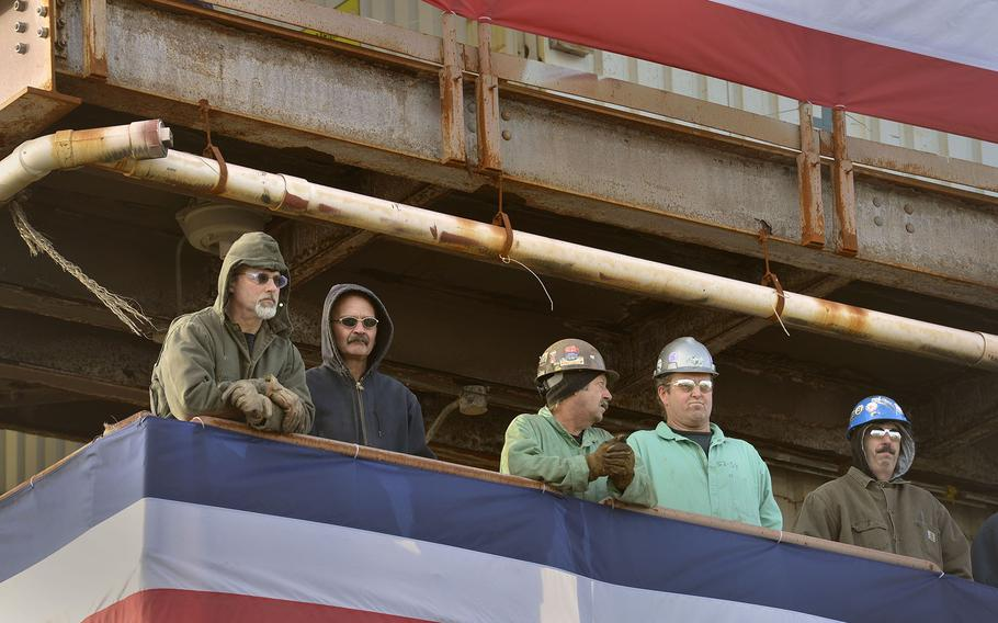 Shipyard workers look on from a lofty perch during a Nov. 21, 2013, ceremony at Bath Iron Works in Brunswick, Maine, Nov. 21, 2013.