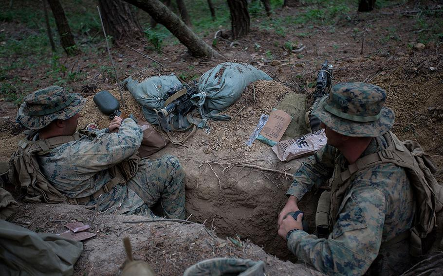 U.S. Marines and sailors assigned to India Company, 3rd Battalion, 8th Marine Regiment, forward deployed to the 3rd Marine Division, as part of the forward Unit Deployed Program, dig two man fighting holes in a defensive position at Camp Mujuk, South Korea, May 31, 2017.