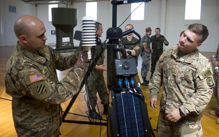 U.S. Air Force Airman 1st Class Athon Arant, right, observes Master Sgt. Steven Hollatz connecting a radio modem to a Tactical Meteorological Observing System during Exercise Cadre Focus 17-1 at McCully Barracks, Germany, on Wednesday, June 14, 2017.