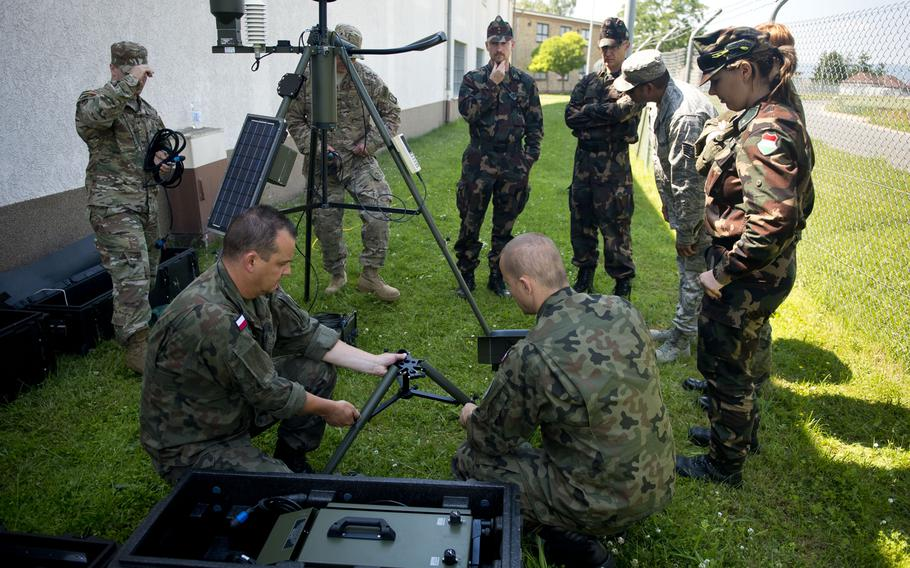 U.S. airmen, Polish soldiers and Hungarian soldiers assemble a Tactical Meteorological Observing System during Exercise Cadre Focus 17-1 at McCully Barracks, Germany, on Wednesday, June 14, 2017.
