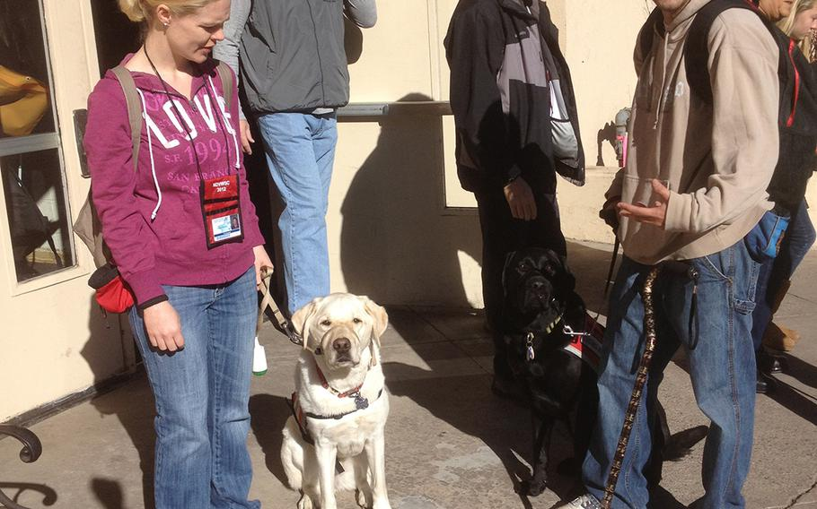 In an undated file photo, Alexis Courneen and her service dog, Sooner, pause outside a veterans event
