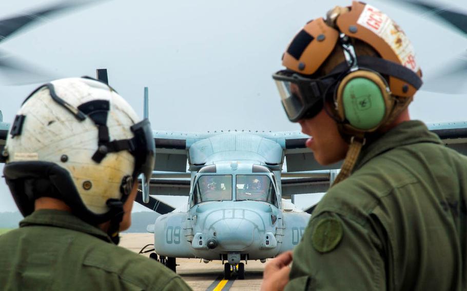 Marine Cpl. Brandon Guico, a Marine Medium Tiltrotor Squadron 262 airframe aerial observer, and William Payne, a VMM-262 avionics technician, watch an MV-22 Osprey take off at Misawa Air Base, Japan, July 31, 2017.