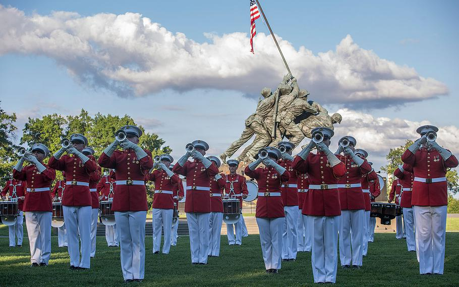 """Marines with """"The Commandant's Own"""" U.S. Marine Drum & Bugle Corps perform """"music in motion"""" during a Tuesday Sunset Parade at the Marine Corps War Memorial, Arlington, Va., July 25, 2017."""