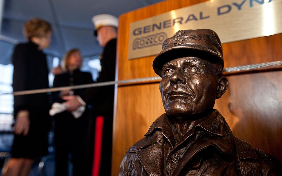 """A statue of Lt. Gen. Lewis """"Chesty"""" Burwell Puller sits as Commandant of the Marine Corps Gen. Joseph F. Dunford Jr., back center, talks with Martha Puller Downs, second left, and Janice Brinkley during the USNS Lewis B. Puller (MLP 3 AFSB) christening ceremony at San Diego, Calif., Feb. 7, 2015."""