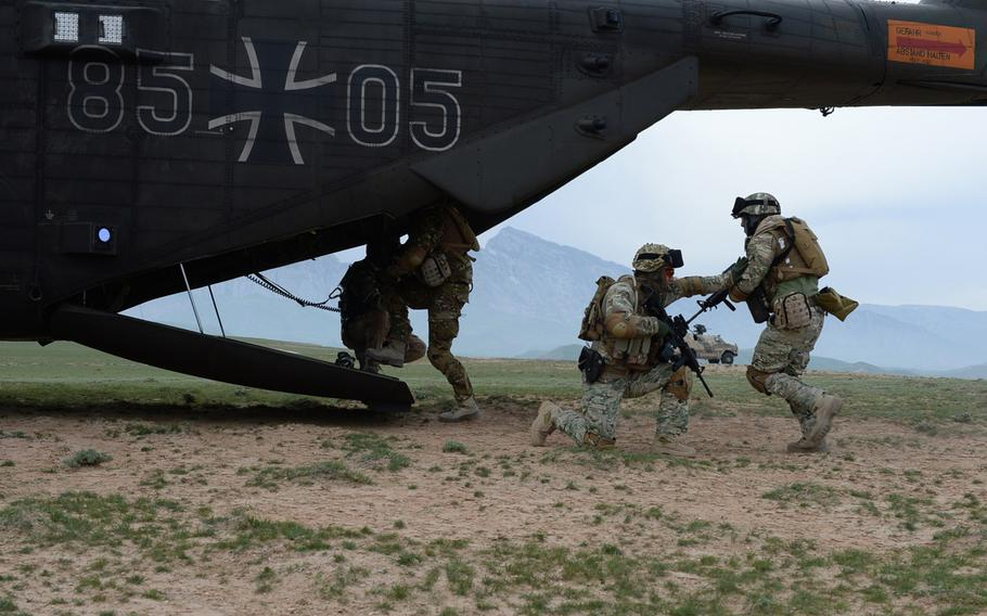 A Georgian soldier provides cover as members of Train, Advise and Assist Command-North's Quick Reaction Force climb aboard a German helicopter in 2015.