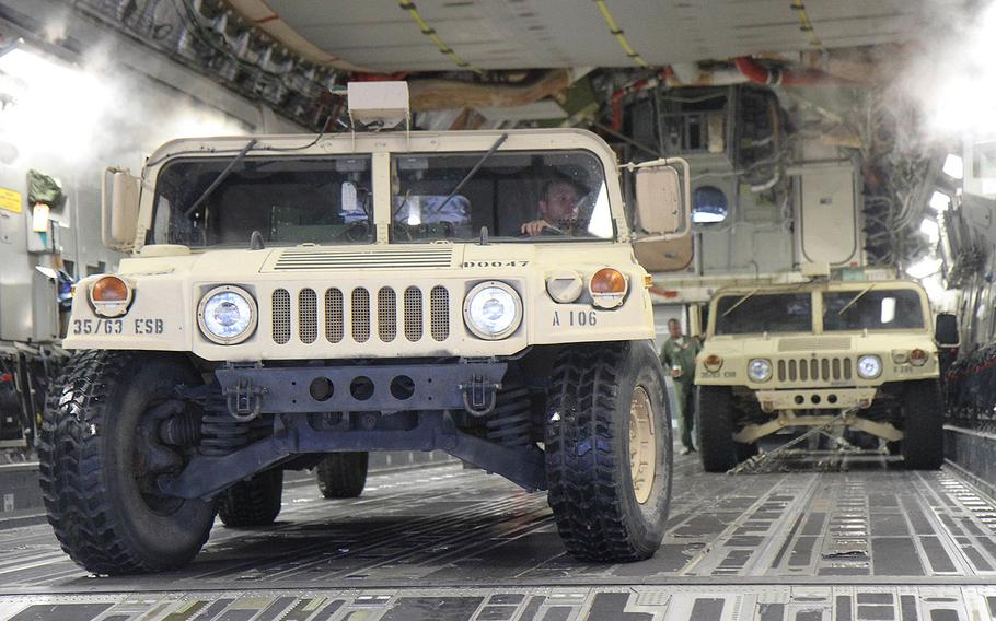 Soldiers assigned to C Company, 63rd Expeditionary Signal Battalion, 35th Theater Tactical Signal Brigade move vehicles and equipment onto a C-17 Globemaster III at Hunter Army Airfield in Georgia before their relief deployment to Texas in support of Hurricane Harvey.