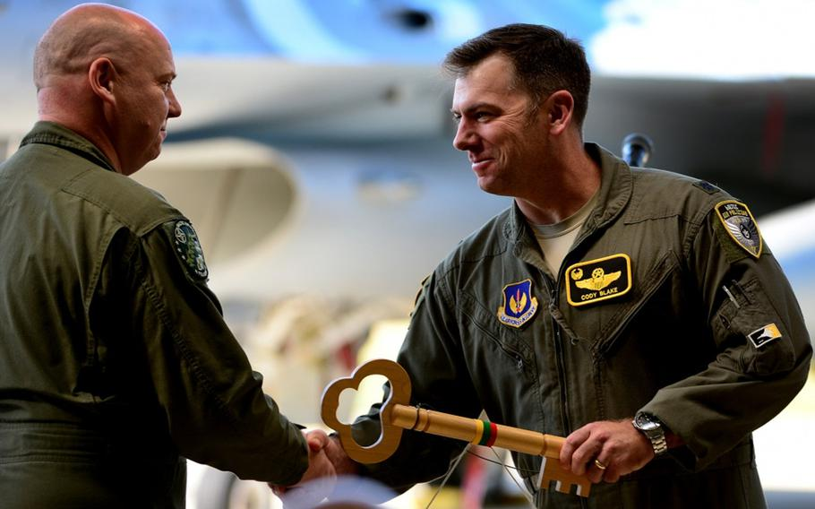 U.S. Air Force Lt. Col. Cody Blake, 493rd Expeditionary Fighter Squadron detachment commander, accepts the key to the Baltic Air Policing mission from Polish air force Lt. Col. Piotr Ostrouch during the official Baltic Air Policing hand-over, take-over ceremony at Siauliai Air Base, Lithuania, Aug. 30, 2017.