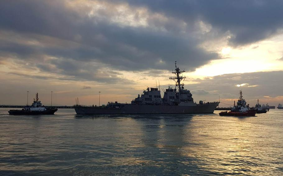 The USS John S. McCain is towed away from the pier at Changi Naval Base, Singapore, to meet the heavy-lift transport vessel MV Treasure, Thursday, Oct. 5, 2017.