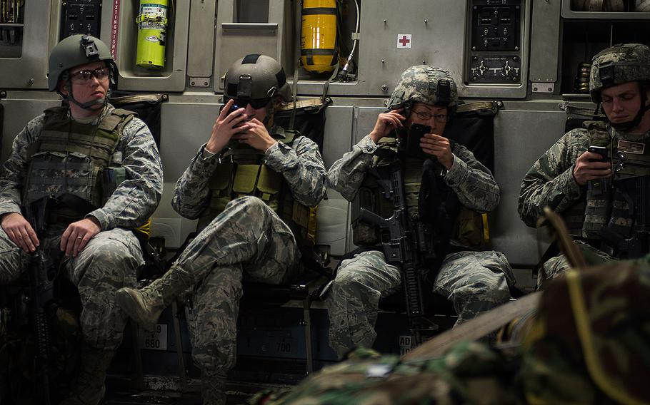 Airmen check their cellphones during a flight aboard a C-17 Globemaster III on Jan. 13, 2014.