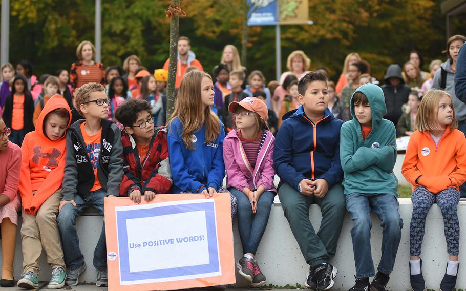 """Students at Ramstein Intermediate School in Germany hold a plaque reading """"Use Positive Words!"""" while participating in the school's Unity Day celebration on Wednesday, Oct. 18, 2017. Many students wore orange, the color typically worn on Unity Day, to symbolize inclusion, acceptance and kindness."""