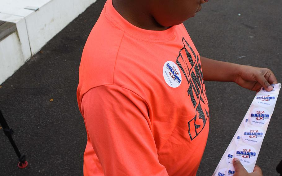 """Josiah Williams, a fifth-grader at Ramstein Intermediate School in Germany, prepares to hand out """"Stop Bullying Now"""" stickers during the school's celebration of Unity Day on Oct. 18, 2017."""