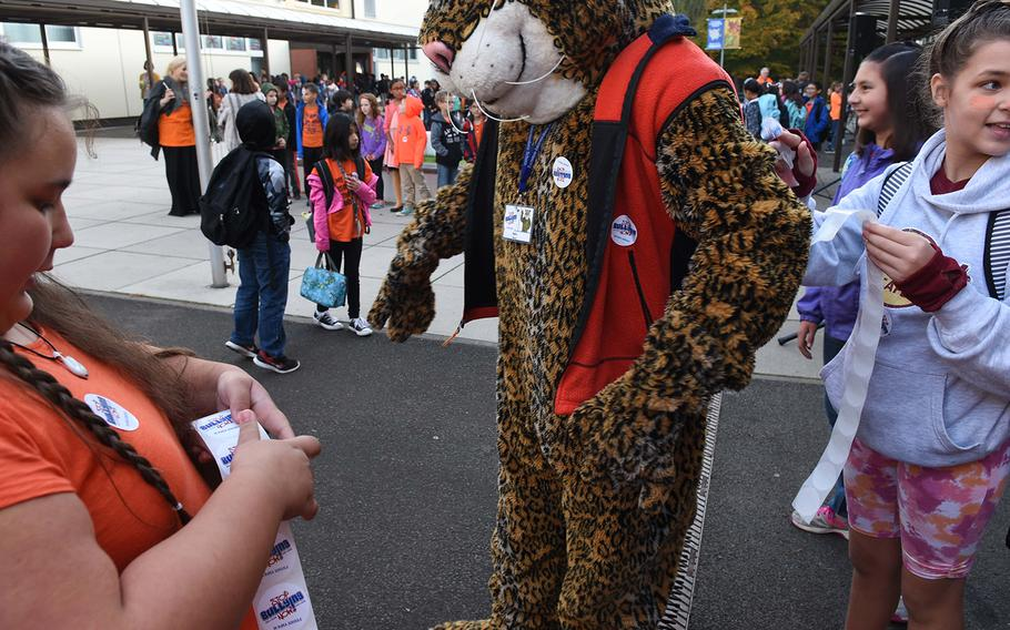 """Ramstein Intermediate School fifth-graders Lucy Baxter, left, and Britain Gonzales put """"Stop Bullying Now"""" stickers on the school's mascot during the school's celebration of Unity Day on Wednesday, Oct. 18, 2017, in Germany."""