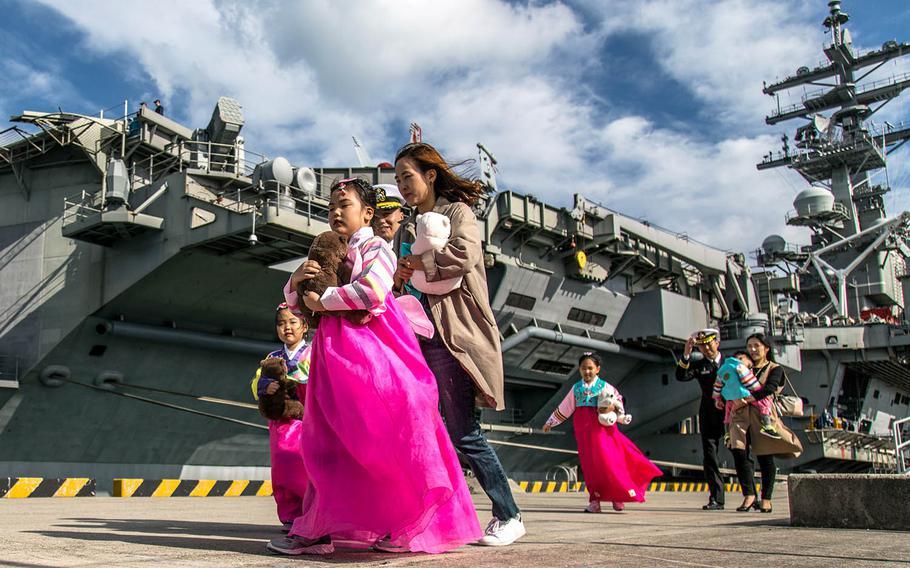 South Korean girls in traditional dress walk by the USS Ronald Reagan at Busan, South Korea, Saturday, Oct. 21, 2017.