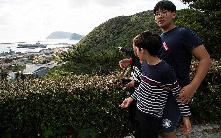 South Koreans watch the USS Ronald Reagan as it arrives in Busan, South Korea, Saturday, Oct. 21, 2017.