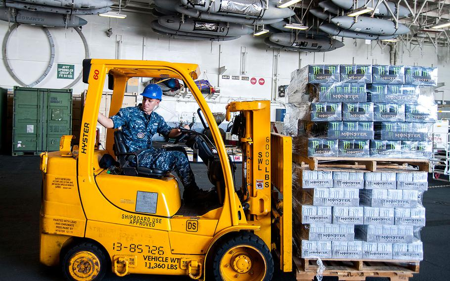 Petty Officer 3rd Class T. A. Sharp moves pallets of energy drinks through the hangar bay of the aircraft carrier USS Harry S. Truman in Norfolk, Virginia on Aug. 17, 2015.