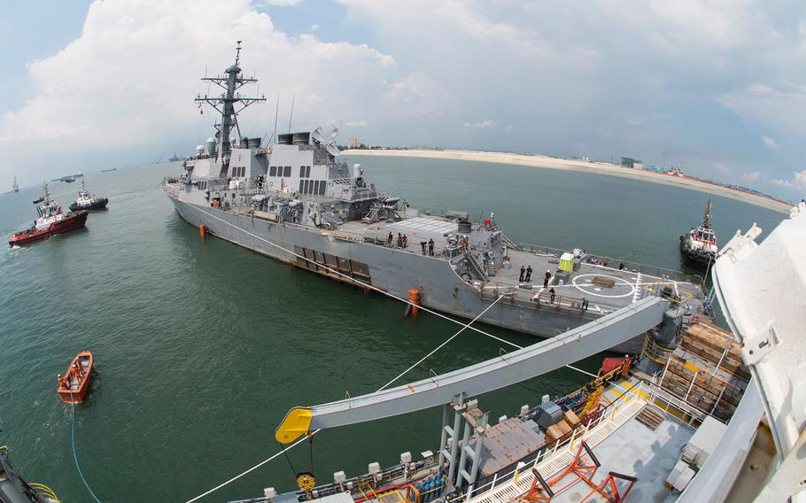The Arleigh Burke-class guided missile destroyer USS John S. McCain is towed out to sea to meet the heavy lift transport vessel MV Treasure, Oct. 6, 2017.