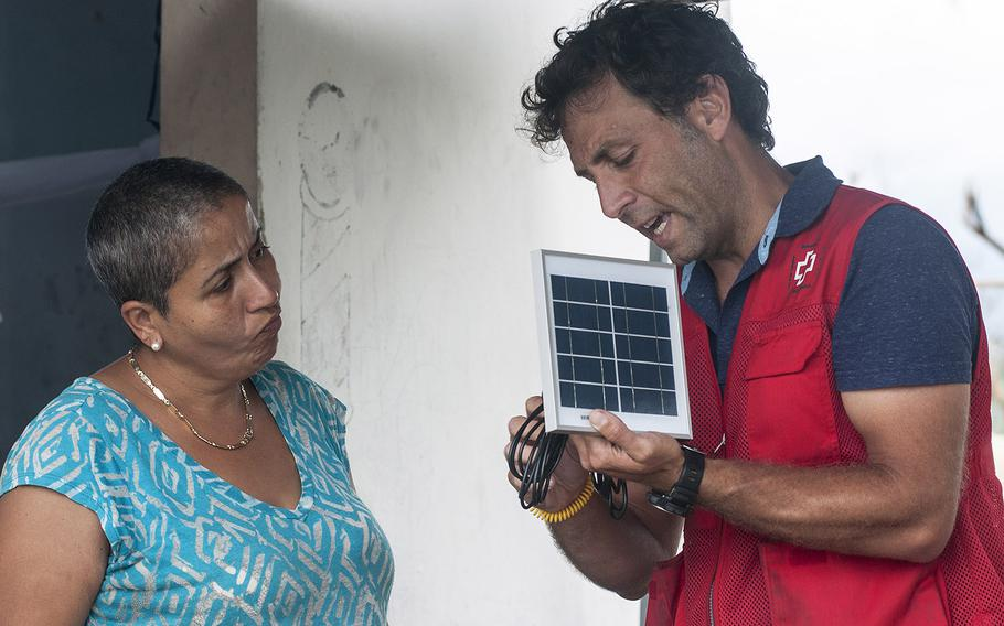 Margaret de Jesus watches as Red Cross volunteer Leando Taraborrelli shows how to use a solar-powered lamp, one of many that were being distributed to residents of the Comerio region of Puerto Rico, on Thursday, Nov. 9, 2017.