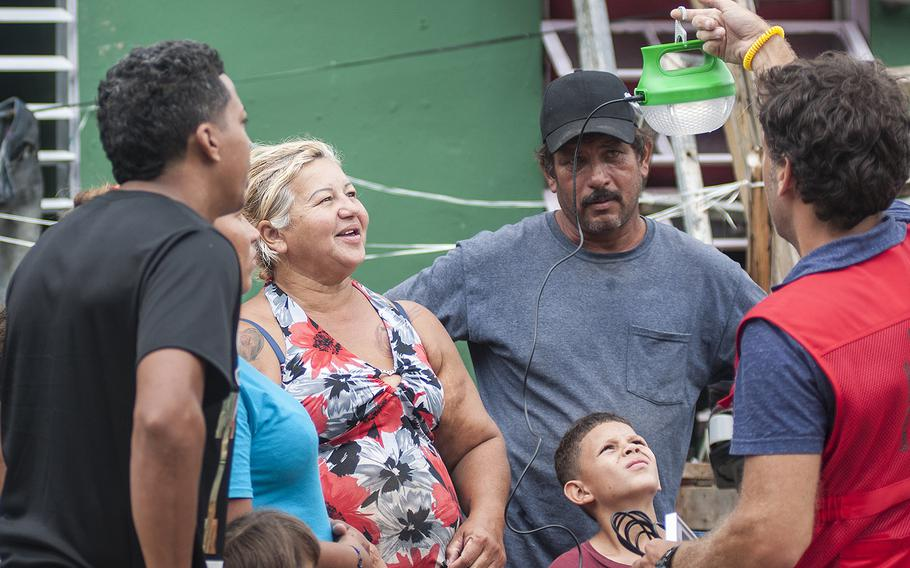 Members of one family in the Comerio region of Puerto Rico watch as a lamp lights up from energy produced by a solar panel. The family received the lamp and a water purifying system on Thursday, Nov. 9, 2017, as a team of Red Cross volunteers visited the area.