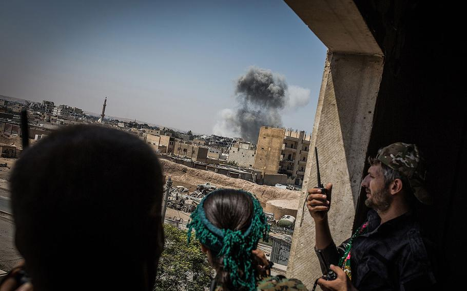 Syrian Democratic Forces soldiers look at smoke rising after an air attack while battles against Islamic State continue in Raqqa, Syria, on Aug. 12, 2017.