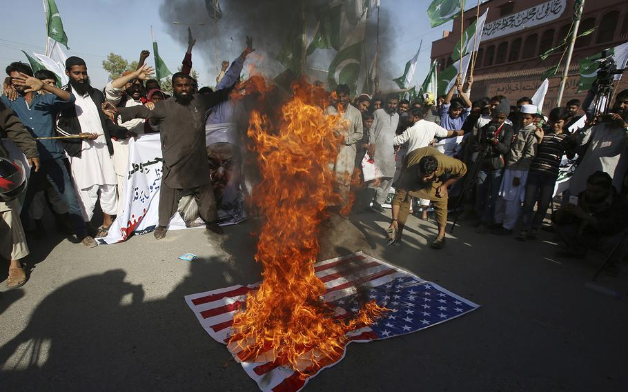 Supporters of Pakistani religious groups burn a representation of an American flag at a rally to condemn a tweet by U.S. President Donald Trump, in Karachi, Pakistan, Tuesday, Jan. 2, 2018.