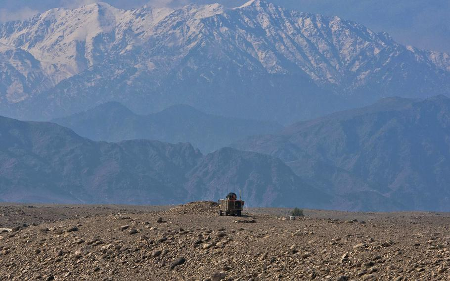 In a 2011 file photo, the mountains of Tora Bora loom over a lone U.S. mine resistant ambush protected vehicle as it patrols outside the Achin District Center.
